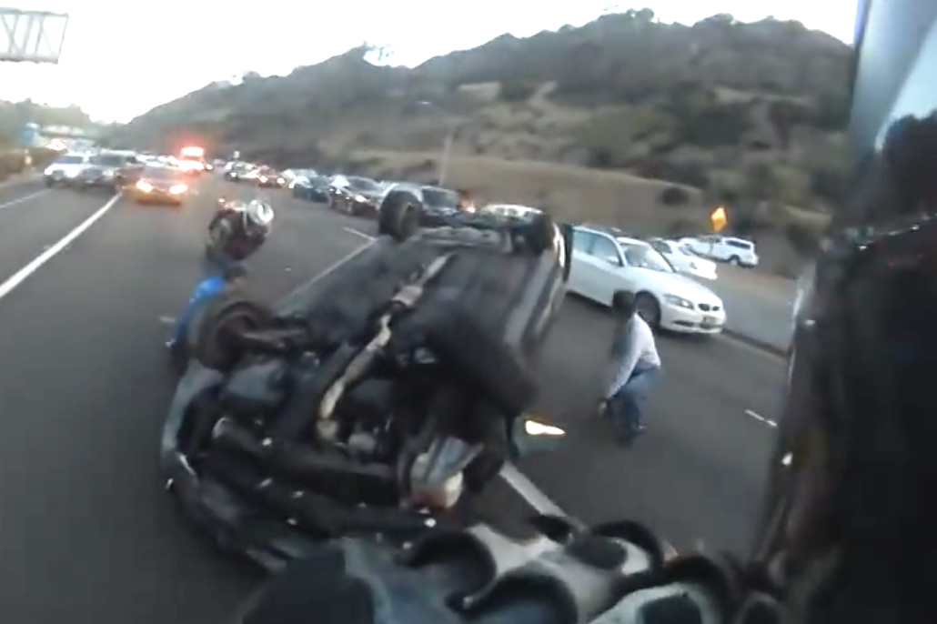 Video: Motorcyclist cuts driver free from overturned car