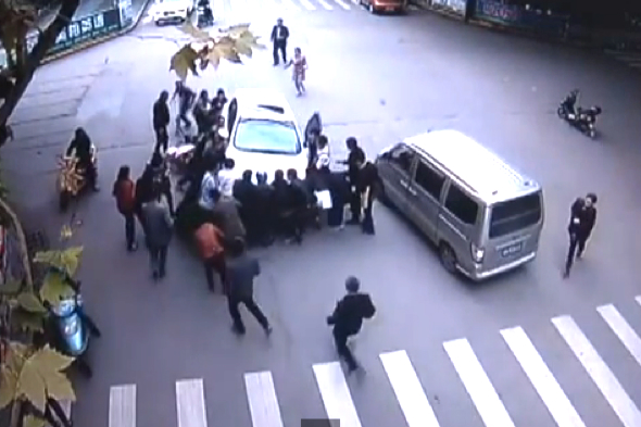 Video: Passers-by lift car off woman after being knocked off scooter
