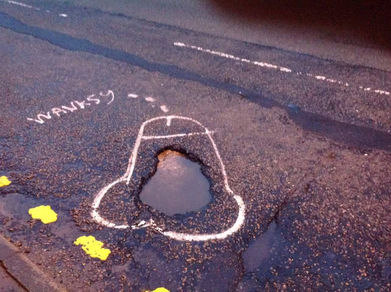 Campaigner highlights potholes by drawing penises around them