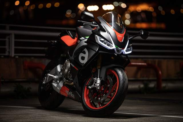 Aprilia RS660 parked up at night with the headlights on