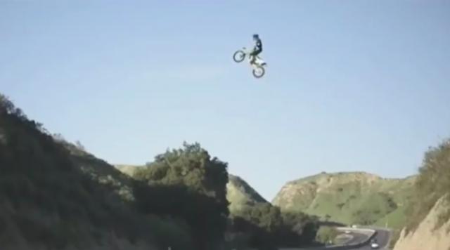 Crazy rider jumps dirt bike over motorway